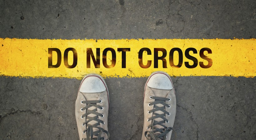 """standing at a line that says """"do not cross"""""""