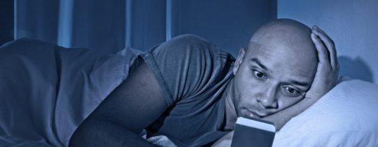 man staring at cell phone in bed